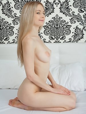"""""""Aside from her stunning body, Lenore captures our attention with her youthful allure as she poses sensually on the bed."""""""